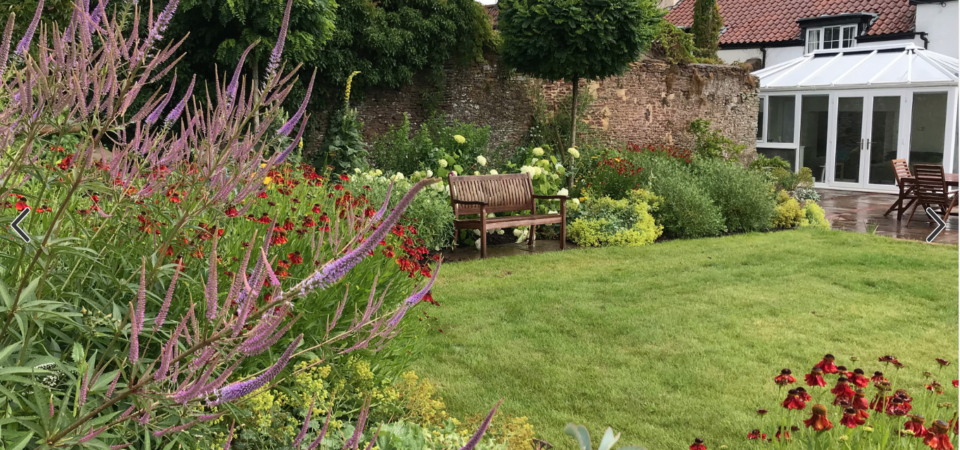 Beautiful Traditional Garden in Gloucestershire with purple flowers and a bench at the rear of a large house
