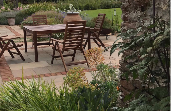 Beautiful traditional garden in Gloucestershire with brown table and four chairs